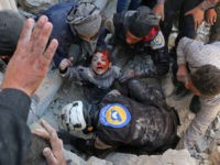 TOPSHOT - Syrian civil defence volunteers, known as the White Helmets, rescue a boy from the rubble following a reported barrel bomb attack on the Bab al-Nairab neighbourhood of the northern Syrian city of Aleppo on November 24, 2016. / AFP / AMEER ALHALBI        (Photo credit should read AMEER ALHALBI/AFP/Getty Images)