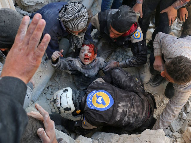 TOPSHOT - Syrian civil defence volunteers, known as the White Helmets, rescue a boy from the rubble following a reported barrel bomb attack on the Bab al-Nairab neighbourhood of the northern Syrian city of Aleppo on November 24, 2016. / AFP / AMEER ALHALBI (Photo credit should read AMEER ALHALBI/AFP/Getty …