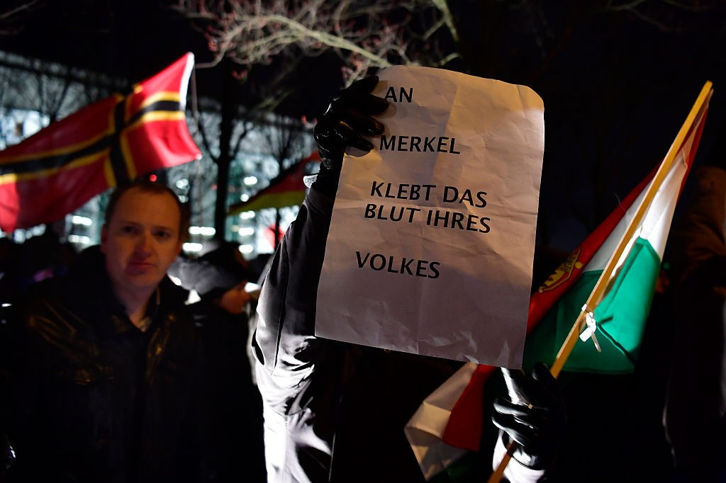 Sympathizers of German populist party AfD hold a placard reading 'Merkel has blood of her nation on her hands' during a prostest rally in front of the chancellory in Berlin, on December 21, 2016, two days after an attack at the Christmas market. After a truck ploughed through a crowd of holiday revellers in central Berlin, the country -- having so far been spared large-scale attacks -- is debating the balance between security and an open society. / AFP / John MACDOUGALL