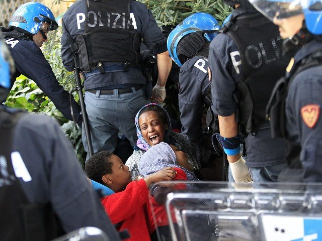 Italian police officers surround a family of migrants during an operation to remove them from the Italian-French border in the Italian city of Ventimiglia on June, 16, 2015. Italy and France engaged in a war of words as a standoff over hundreds of Africans offered a graphic illustration of Europe's …