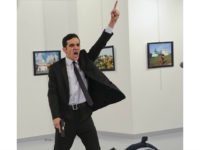 FILE - In this Monday, Dec. 19, 2016 file photo, Mevlut Mert Altintas shouts after shooting Andrei Karlov, right, the Russian ambassador to Turkey, at an art gallery in Ankara, Turkey. At first, AP photographer Burhan Ozbilici thought it was a theatrical stunt when a man in a dark suit and tie pulled out a gun during the photography exhibition. The man then opened fire, killing Karlov. (AP Photo/Burhan Ozbilici)