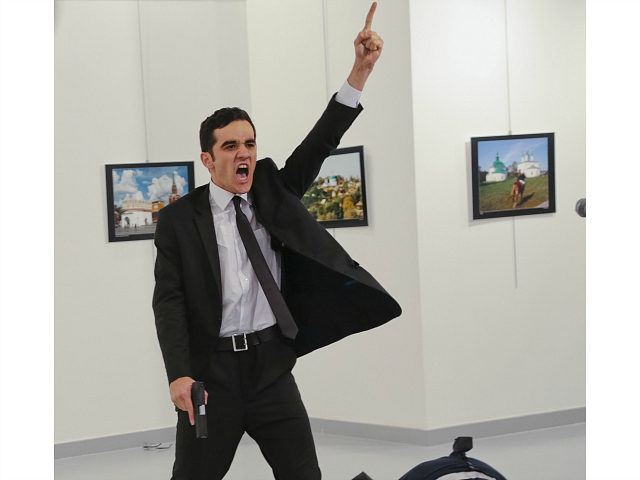 FILE - In this Monday, Dec. 19, 2016 file photo, Mevlut Mert Altintas shouts after shooting Andrei Karlov, right, the Russian ambassador to Turkey, at an art gallery in Ankara, Turkey. At first, AP photographer Burhan Ozbilici thought it was a theatrical stunt when a man in a dark suit …