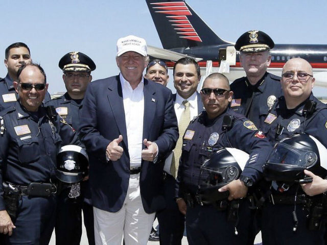 Republican presidential hopeful Donald Trump, center, poses for a photo with Laredo Police officers before Trump's departure from Laredo, Texas, Thursday, July 23, 2015. (AP Photo/LM Otero)