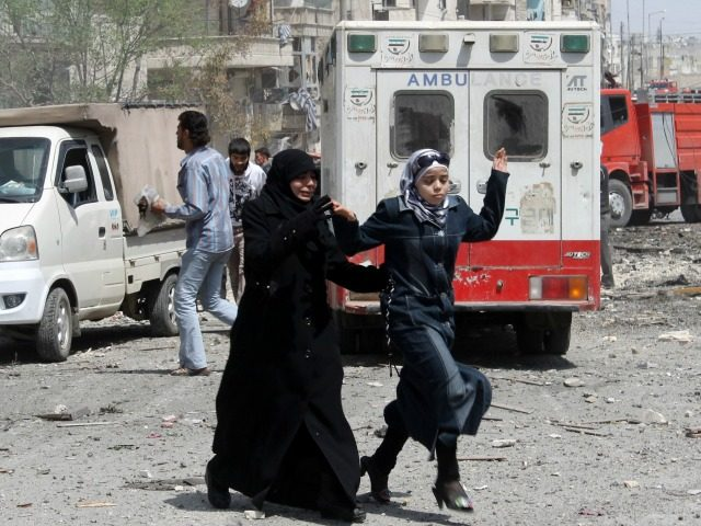Syrians run for cover following a reported barrel-bomb attack by pro-government forces on the Dharat Awad neighbourhood of the northern Syrian city of Aleppo on April 20, 2014. In three years, more than 150,000 people have been killed and nearly half the country's population have fled their homes. AFP PHOTO …