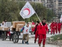 Members of the Syrian Red Crescent escort Syrians and aid supplies from a rebel-controlled area to a regime held area of the northern Syrian city of Aleppo on December 10, 2015 through the Garage al-Hajz crossing in the Bustan al-Qasr district. / AFP / KARAM AL-MASRI (Photo credit should read …