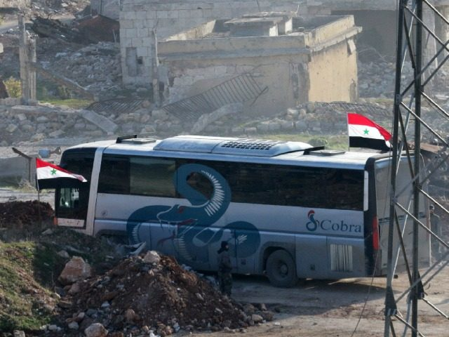 A bus drives through the Syrian government-controlled crossing of Ramoussa, on the southern outskirts of Aleppo, on December 18, 2016, during an evacuation operation of rebel fighters and civilians from rebel-held areas. / AFP / George OURFALIAN (Photo credit should read GEORGE OURFALIAN/AFP/Getty Images)