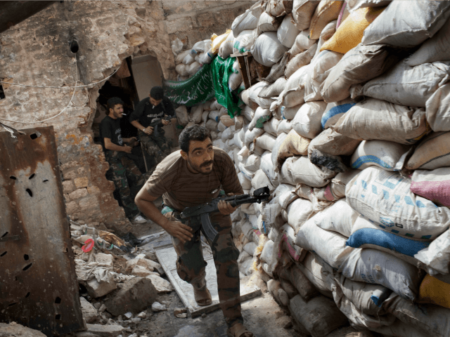 Rebel fighters duck as they run behind a barricade to avoid being fired at by Syrian regime forces in the Old City's front line in Aleppo on September 18, 2013. Damascus and key ally Moscow joined forces in a bid to thwart plans for a Western-backed UN resolution on Syria's …