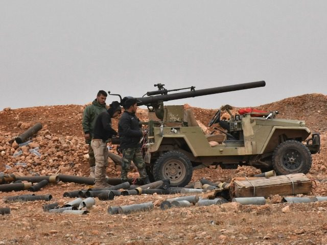 Syrian pro-government forces stand next to a 106mm recoilless anti-tank cannon as residents (unseen) fleeing the eastern part of Aleppo arrive at the Jabal Badro crossing point, which was recently retaken from rebel fighters by the regime forces, on November 30, 2016.