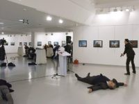 This picture taken on December 19, 2016 shows Andrei Karlov (2ndR), the Russian ambassador to Ankara, lying on the floor after being shot by Mevlut Mert Altintas (R) during an attack during a public event in Ankara. A gunman crying 'Aleppo' and 'revenge' shot Karlov while he was visiting an …