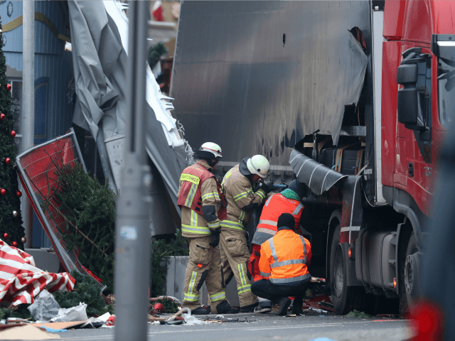 Rescue workers begin to remove the rear of the lorry the morning after it ploughed through a Christmas market on December 20, 2016 in Berlin, Germany. Several people have died while dozens have been injured as police investigate the attack at a market outside the Kaiser Wilhelm Memorial Church on …