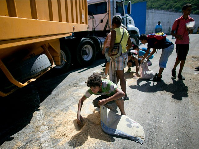 In this Nov. 14, 2016 photo, a youth uses his pillow as a bag to collect rice from the pavement that shook loose from a food cargo truck waiting to enter the port in Puerto Cabello, Venezuela, the port that handles the majority of Venezuela's food imports. As millions of …