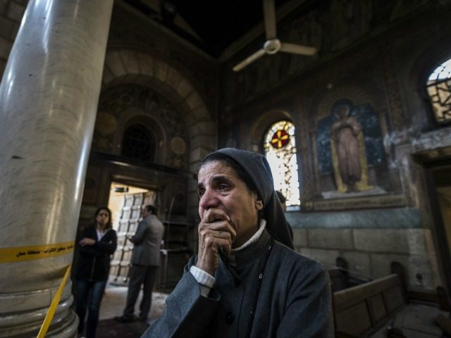 A nun reacts as Egyptian security forces (unseen) inspect the scene of a bomb explosion at the Saint Peter and Saint Paul Coptic Orthodox Church on December 11, 2016, in Cairo's Abbasiya neighbourhood. The blast killed at least 25 worshippers during Sunday mass inside the Cairo church near the seat …