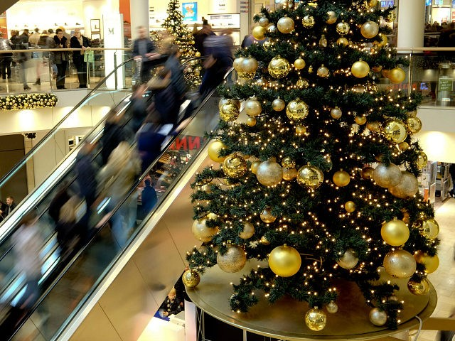 Shoppers on an escaltor pass by a Christmas tree on a Special Shopping Sunday in the Stadtgalerie in Hameln, Germany, 27 December 2015. Photo: Peter Steffen/dpa Peter Steffen / DPA