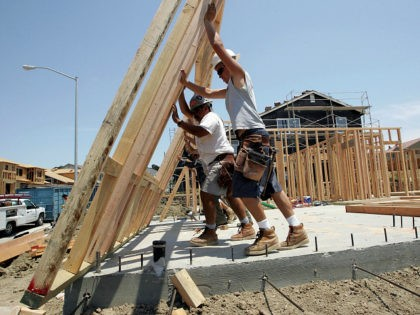 RICHMOND, CA - JUNE 26: Construction workers raise wood framing as they build homes in a new housing development June 26, 2006 in Richmond, California. A report issued by the U.S. Commerce Department stated that sales of new single-family homes were up 4.6 percent in May. The median price of …