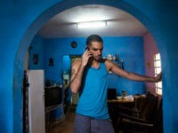 Danilo Maldonado, better known as El Sexto, speaks on a mobile phone in the living room of his home after being released from jail, in Havana, Cuba, Tuesday, Oct. 20, 2015. Maldonado was freed after 10 months behind bars for attempting to release two pigs painted with the names of Raul and Fidel Castro, the country's current president and former leader. (AP Photo/Desmond Boylan)