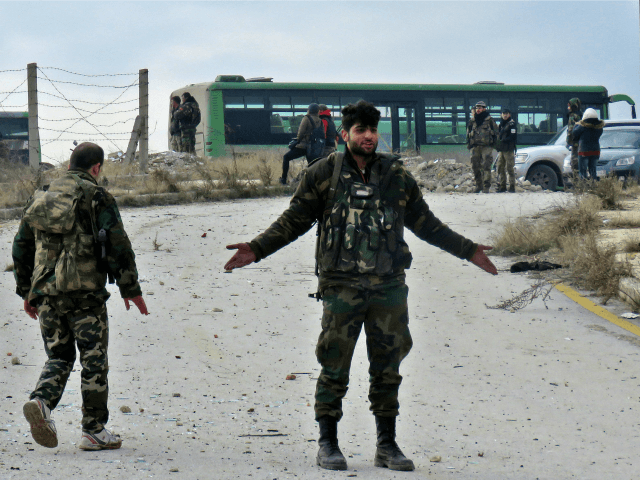 A syrian soldier gestures during the evacuation of insurgents from a rebel-held area of Aleppo towards rebel-held territory in the west of Aleppo's province on December 16, 2016. Russia announced it was negotiating with the Syrian opposition and seeking a nationwide ceasefire, as the evacuation of civilians and fighters from …