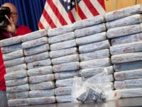A firearm and 154 pounds of heroin worth at least $50 million are displayed at a Drug Enforcement Administration news conference, Tuesday, May 19, 2015 in New York. The DEA called the heroin seizure its largest ever in New York state. Officials said on Tuesday that most of the drugs …