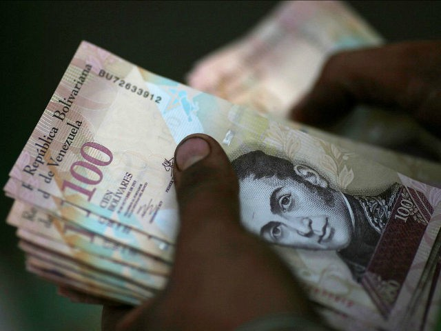 A cashier counts Venezuelan bolivar notes at a street market in downtown Caracas, Venezuela, December 12, 2016. REUTERS/Ueslei Marcelino