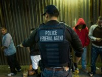 A U.S. Immigration and Customs Enforcement (ICE) agent directs a group of undocumented men being deported to Mexico at the U.S.-Mexico border in San Diego, California, U.S., on Thursday, Feb. 26, 2015. The U.S. Department of Homeland Security is nearing a partial shutdown as the agency's funding is set to …