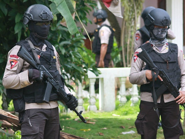 CORRECTION - Armed police secure a house after a firefight erupted as alleged militants had opened fire at officers in South Tangerang, 25 kilometres (15 miles) outside the capital Jakarta, on December 21, 2016. Indonesian police have foiled plans for a Christmas suicide bombing after killing three suspected militants on …