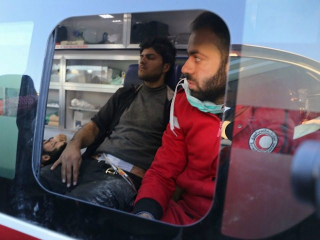Wounded Syrian men who were evacuated from rebel-held neighbourhoods in the embattled city of Aleppo, sit in a Syrian Arab Red Crescent ambulance upon their arrival in the opposition-controlled Khan al-Aassal region, west of the city, on December 15, 2016, which is the first stop on their trip, where humanitarian …