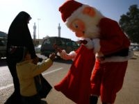 A man dressed in a Santa Claus outfit hands a souvenir to an Iraqi Muslim boy in the Shiite holy city of Najaf on December 17, 2015. AFP PHOTO / HAIDAR HAMDANI / AFP / HAIDAR HAMDANI (Photo credit should read HAIDAR HAMDANI/AFP/Getty Images)