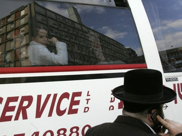 A woman looks out of the window of a bus as Jerusalem's Hadassah hospital is reflected on the glass 09 January 2006. Israeli Prime Minister Ariel Sharon was breathing unassisted today while being gradually awoken from a deep coma so doctors can assess the extent of damage to his brain …