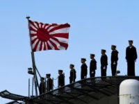 Sailors stand on the deck of the Izumo warship as it departs from the harbor of the Japan United Marine shipyard in Yokohama, south of Tokyo. March 25, 2015. REUTERS/Thomas Peter