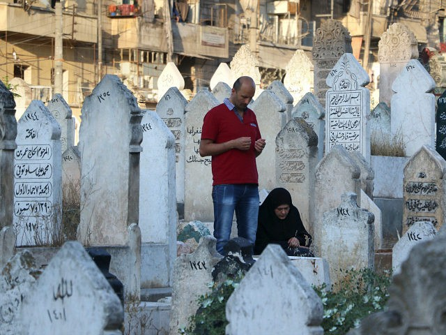 ALEPPO, SYRIA - JULY 06 : Muslims visit their relatives tombs at martyrdom after they performed Eid al-Fitr mass prayer during the Eid al-Fitr holiday in Atarib District of Aleppo, Syria on July 06, 2016. Eid al-Fitr is a religious holiday celebrated by Muslims around the world that marks the end of Ramadan, Islamic holy month of fasting. (Photo by Ahmed Hasan Ubeyd/Anadolu Agency/Getty Images)