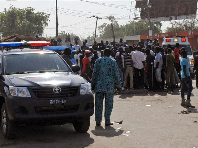Emergency services, police and residents gather at the scene of a suicide bomb attack on a market in Maiduguri, after two girls approximately seven or eight years old blew themselves, killing themselves and wounding at least 17 others. The attack was not immediately claimed by the Boko Haram jihadist insurgency but bore all the hallmarks of the jihadists, who have regularly used women and young girls to carry out suicide attacks in their seven-year insurgent campaign in the troubled region. / AFP / STR (Photo credit should read STR/AFP/Getty Images)