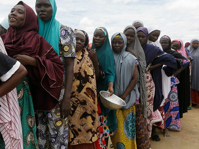 FILE-In this file photo taken Saturday, Aug. 27, 2016, women displaced by Islamist extremists wait for food to be handed out to them at the Bakassi camp in Maiduguri, Nigeria. Many say the dangerous journey is preferable to the hunger, humiliation and inhumane conditions in refugee camps where more than …