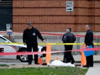Police cover the body of a suspect outside Watts Hall on the campus of Ohio State University in Columbus, Ohio, following an attack on campus that left several people injured on Monday, Nov. 28, 2016. The man, identified as Abdul Razak Ali Artan, plowed his car into a group of pedestrians and began stabbing people with a butcher knife Monday before he was shot to death by a police officer. (Adam Cairns/The Columbus Dispatch via AP)