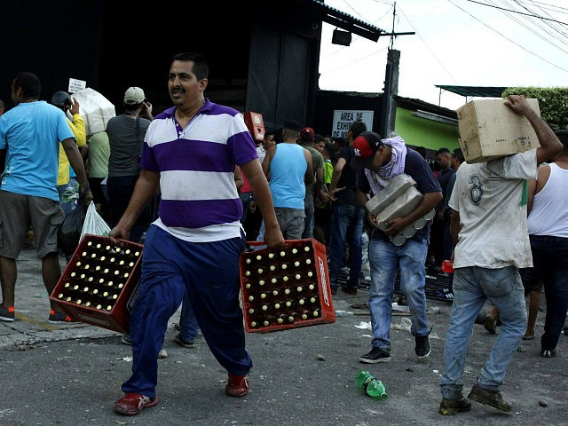 People carry goods taken from a food wholesaler after it was broken into, in La Fria, Venezuela December 17, 2016. REUTERS/Carlos Eduardo Ramirez