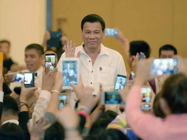 Philippine President Rodrigo Duterte greets members of the Filipino community as he arrives in the Cambodian capital Phnom Penh on December 13, 2016. Duterte is on a two-day state visit to Cambodia. / AFP / TANG CHHIN SOTHY (Photo credit should read TANG CHHIN SOTHY/AFP/Getty Images)