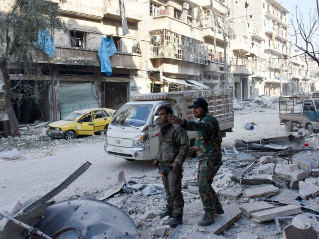 Syrian pro-government forces stand on a street in al-Maadi district of eastern Aleppo on December 11, 2016 after they retook a large part of it from rebel fighters. Thousands of civilians poured out of rebel areas of Aleppo as Syria's army pushed to take the last remnants of opposition-held territory …