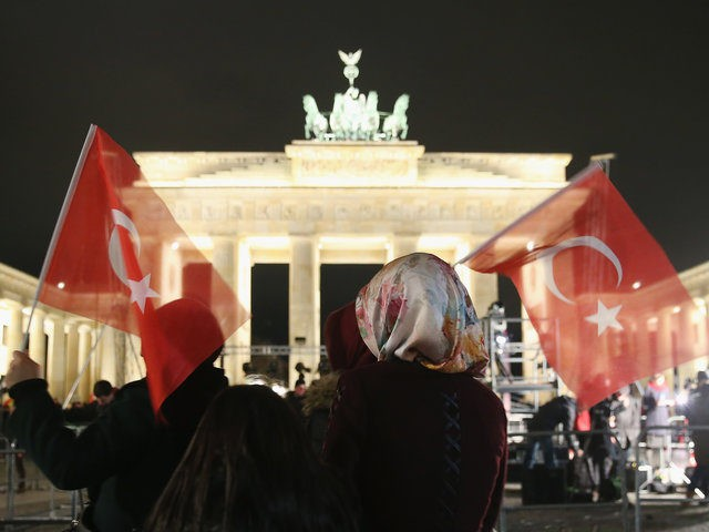 BERLIN, GERMANY - JANUARY 13: Young Muslim women wearing headscarves and holding Turkish flags walk past the Brandenburg Gate following a vigil organized by Muslim groups to commemorate the victims of the recent terror attacks in Paris on January 13, 2015 in Berlin, Germany. Germany is home to four million …