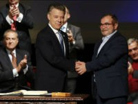Colombia's President Juan Manuel Santos, front left, shakes hands with Rodrigo Londono, known as Timochenko, top leader of the Revolutionary Armed Forces of Colombia, FARC, after signing a revised peace pact at Colon Theater in Bogota, Colombia, Thursday, Nov. 24, 2016. An original accord ending the half century conflict was rejected by voters in a referendum last month. (AP Photo/Fernando Vergara)