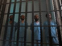 Prisoners stand in their holding cell at the court room of a state security court during their trial on March 2, 2014 in the Yemeni capital Sanaa. The defendants, two of them being tried in absentia, are charged with forming part -- between 2011 and 2013 -- of 'an armed …