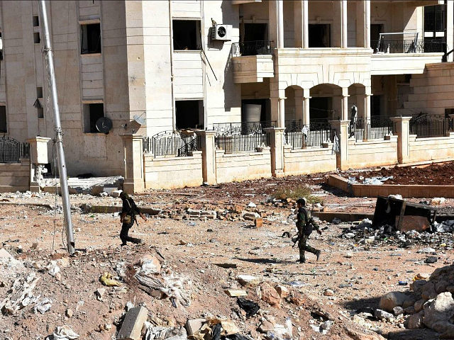 Syrian pro-government soldiers cross a road '3000' apartment block area, in al-Hamdaniyah, in eastern Aleppo on November 4, 2016. Syrian rebels fired rockets at one of the eight evacuation corridors opened from opposition-held east Aleppo during a unilateral Russian-declared ceasefire, Syrian state television reported. / AFP / GEORGE OURFALIAN (Photo …