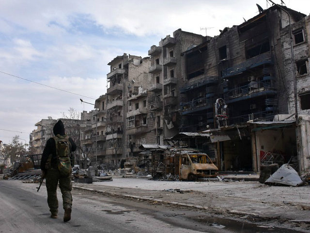 Syrians regime forces walk past destroyed buildings in the former rebel-held Ansari district in the northern city of Aleppo on December 23, 2016 after Syrian government forces retook control of the whole embattled city. Syrian troops cemented their hold on Aleppo after retaking full control of the city, as residents …