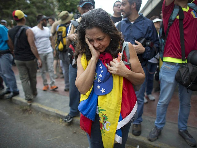 An anti-government protester holds a Venezuelan flag as security forces block the opposition from reaching the National Electoral Council (CNE) in Caracas, Venezuela, Wednesday, May 11, 2016. The opposition is marching to demand election officials start counting signatures that could lead to a presidential recall vote. (AP Photo/Ariana Cubillos)