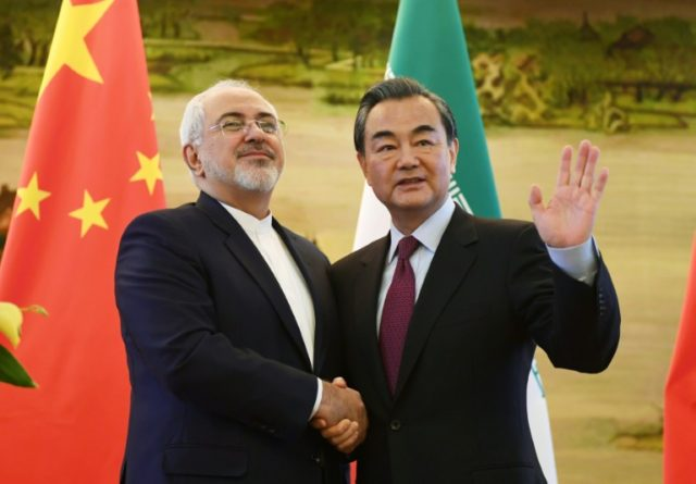 Iran's Foreign Minister Mohammad Javad Zarif (L) shakes hands with his Chinese counterpart Wang Yi after a joint press conference in Beijing, on December 5, 2016