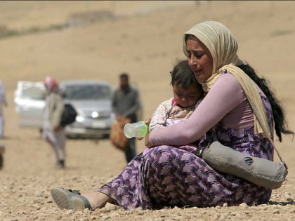 A displaced woman and child from the minority Yazidi sect, fleeing violence from forces loyal to the Islamic State in Sinjar town, rest as they make their way towards the Syrian border, on the outskirts of Sinjar mountain, near the Syrian border town of Elierbeh of Al-Hasakah Governorate August 10, …