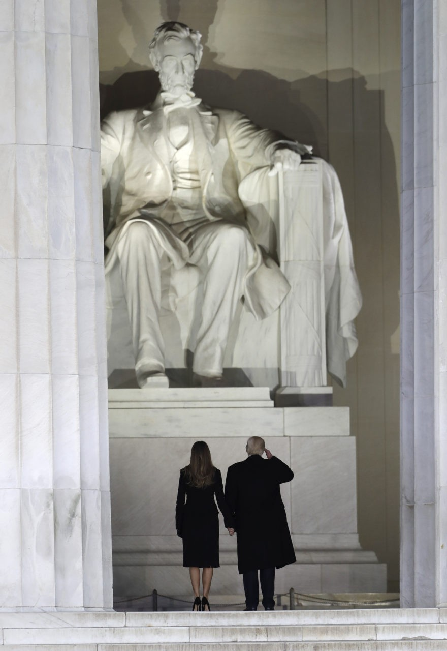 """President-elect Donald Trump salutes Lincoln with his wife Melania Trump as they arrive at a pre-Inaugural """"Make America Great Again! Welcome Celebration"""" at the Lincoln Memorial in Washington, Thursday, Jan. 19, 2017. (AP Photo/David J. Phillip)"""