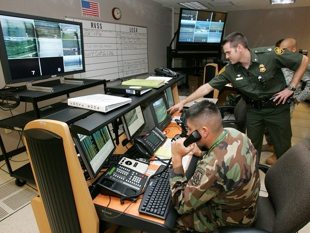 U.S. Border Patrol Assistant Patrol Agent in Charge Carl McClafferty, right, and members of the New Mexico National Guard watch remote cameras on the border at the Deming Border Patrol station in Deming, N.M., Wednesday, Aug. 30, 2006. Georgia Gov. Sonny Perdue visited Georgia's National Guard troops helping fortify the …