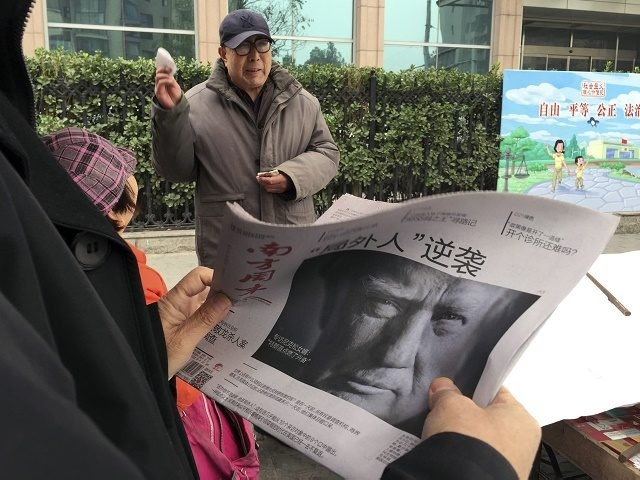 "FILE - In this Nov. 10, 2016 file photo, a Chinese man holds up a Chinese newspaper with the front page photo of U.S. President-elect Donald Trump and the headline ""Outsider counter attack"" at a newsstand in Beijing, China. China views a Trump presidency with less trepidation. It has viewed …"
