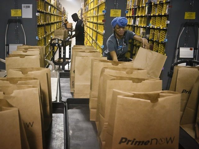 FILE - In this Wednesday Dec. 21, 2016, file photo, Miracle Stewart, right, an employee of Amazon PrimeNow, prepares bags to fill with orders from customers making purchases, at a distribution hub in New York. Amazon said Thursday, Jan. 12, 2017, that it plans to hire 100,000 people across the …