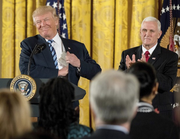 President Donald Trump, accompanied by Vice President Mike Pence, right, smiles as he takes the podium for a White House senior staff swearing in ceremony in the East Room of the White House, Sunday, Jan. 22, 2017, in Washington. (AP Photo/Andrew Harnik)