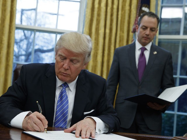 President Donald Trump signs an executive order to withdraw the U.S. from the 12-nation Trans-Pacific Partnership trade pact agreed to under the Obama administration, Monday, Jan. 23, 2017, in the Oval Office of the White House in Washington. (AP Photo/Evan Vucci)