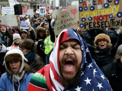 Izzy Berdan, of Boston, center, wears an American flags as he chants slogans with other demonstrators during a rally against President Trump's order that restricts travel to the U.S., Sunday, Jan. 29, 2017, in Boston. Trump signed an executive order Friday, Jan. 27, 2017 that bans legal U.S. residents and …